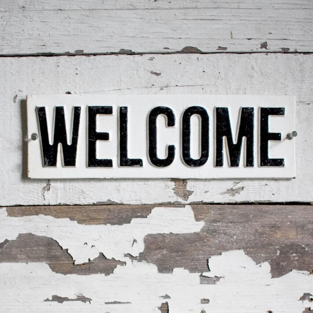 White lettering on white painted cast iron of the word Welcome