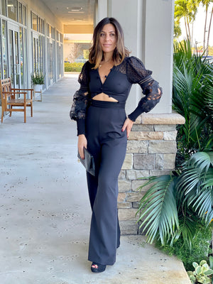 Black jumpsuit features a pom pom trim along with the neckline and cutout detail at the center front.