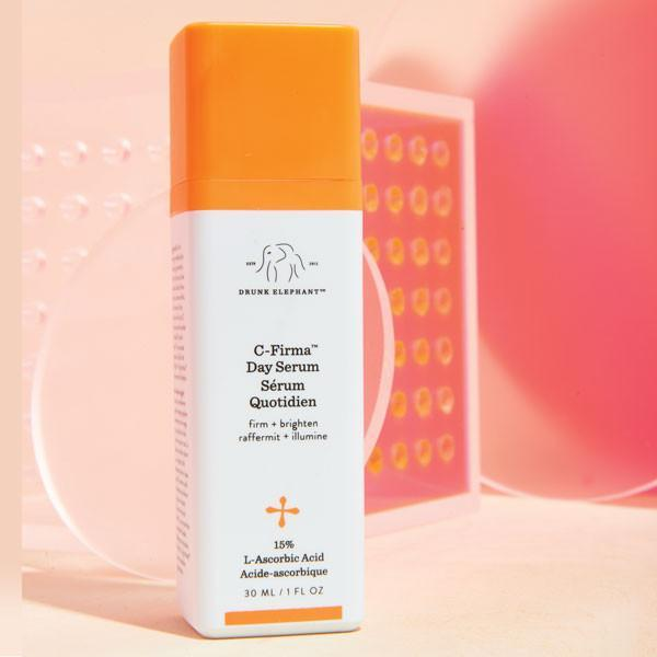 Stylized C-Firma Day Serum Image on a light pink and tangerine, textured background