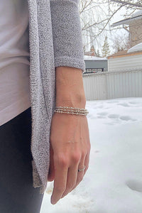 Woman wearing three silver Morse Code Bracelets in the winter