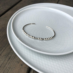 Sterling silver CARPE DIEM Morse Code Bangle on a plate