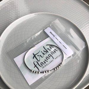 Silver BREATHE Morse Code Bracelet with packaging