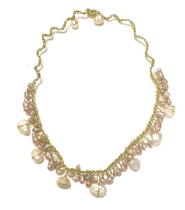 Soft pink pearl necklace on gold yarn