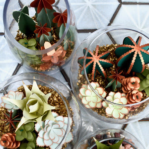 A variety of paper succulents in greens and blues with copper accents are arranged in 3 glass terrariums.