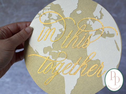 "Circular, layered paper cut collage made of 3 different tones of shimmery, metallic gold cardstock. The bottom two layers make up the image of the earth's surface. The elegant script phrase, ""in this together,"" is cut from textured antique gold foil stock, which beautifully reflects surrounding light."