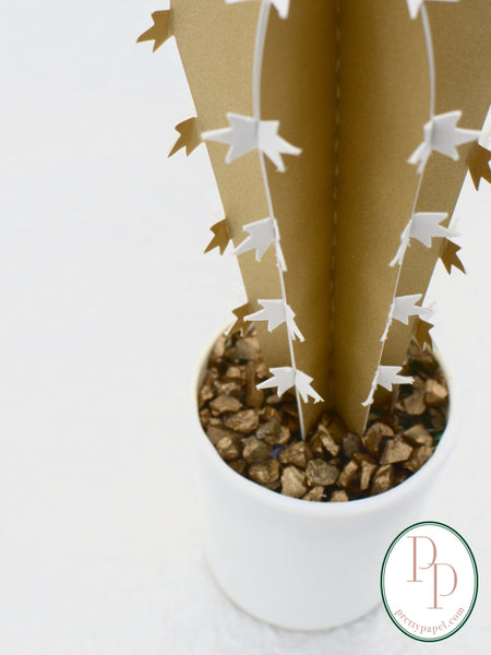 Close up of gold glitter cactus base, planted in a white pot with gold crushed glass medium.