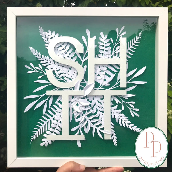 Botanical paper cut collage with woodland foliage and clean, sans serif letters spelling SHIT on top of a bright green background. In white square shadowbox frame.