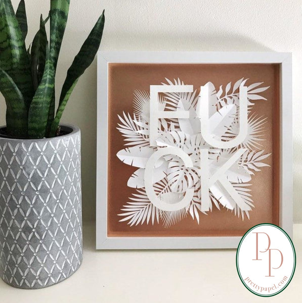 Botanical paper cut collage with tropical foliage and clean, sans serif letters spelling FUCK on top of a metallic copper background. In white square shadowbox frame.