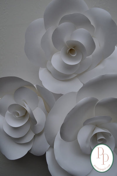 Grouping of 3 oversized white paper roses hanging on a white wall.
