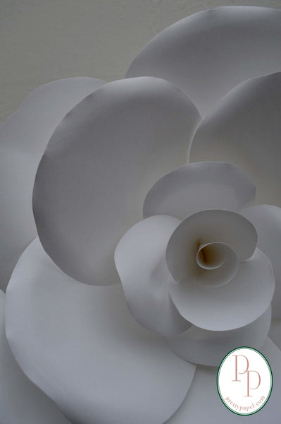 Close up of one oversize paper rose hanging on a white wall.