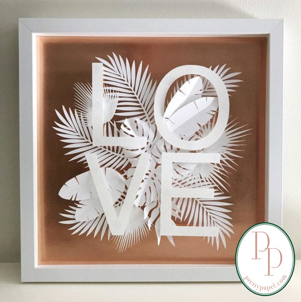 Botanical paper cut collage with tropical foliage and clean, sans serif letters spelling LOVE on top of a metallic copper background. In white square shadowbox frame.