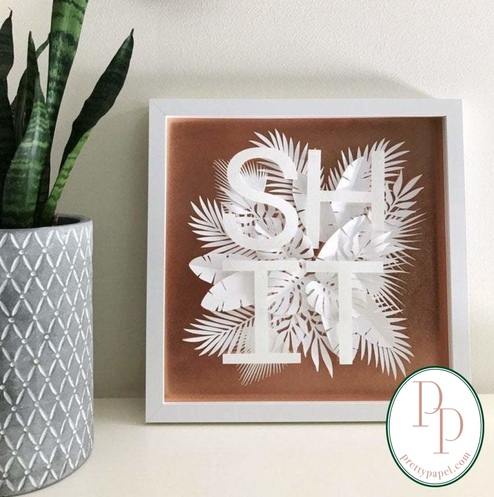 Botanical paper cut collage with tropical foliage and clean, sans serif letters spelling SHIT on top of a metallic copper background. In white square shadowbox frame.