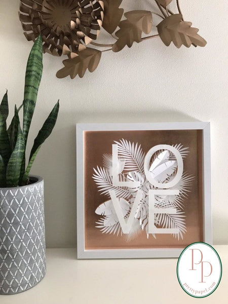 Botanical paper cut collage with tropical foliage and clean, sans serif letters spelling FUCK on top of a metallic copper background. In white square shadowbox frame. Next to snake plant in geomptric cement planter.