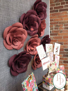 8 oversized paper roses in merlot and dusty rose cardstocks, pinned to a fabrick backdrop in a stationery shop window display.