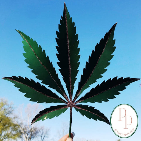Oversize paper Cannabis Sativa leaf, embellished with glitter, held up to a clear blue sky.