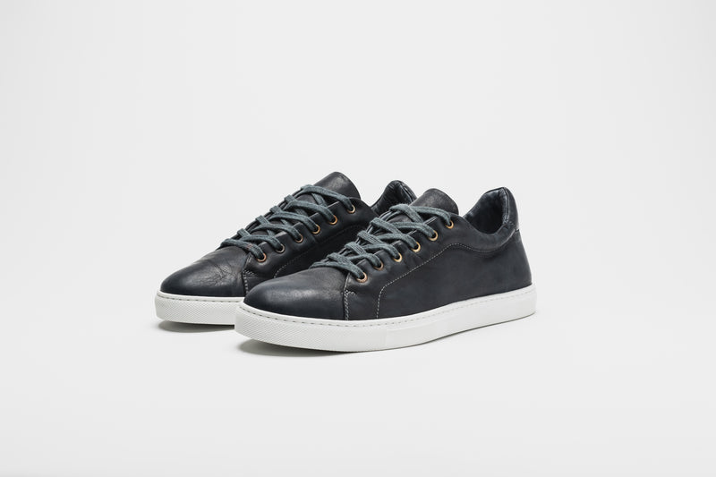 Navy blue men's leather sneakers on white soles with navy blue laces
