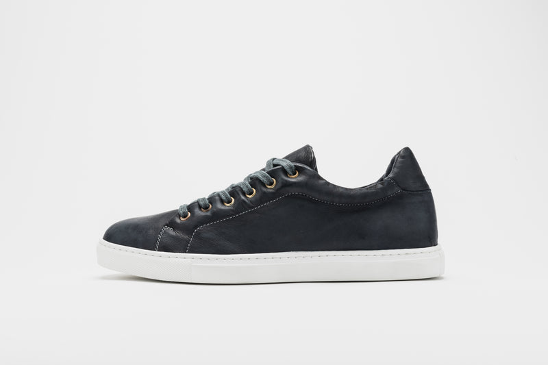 A side image of men's leather sneakers in navy blue leather on a white sole