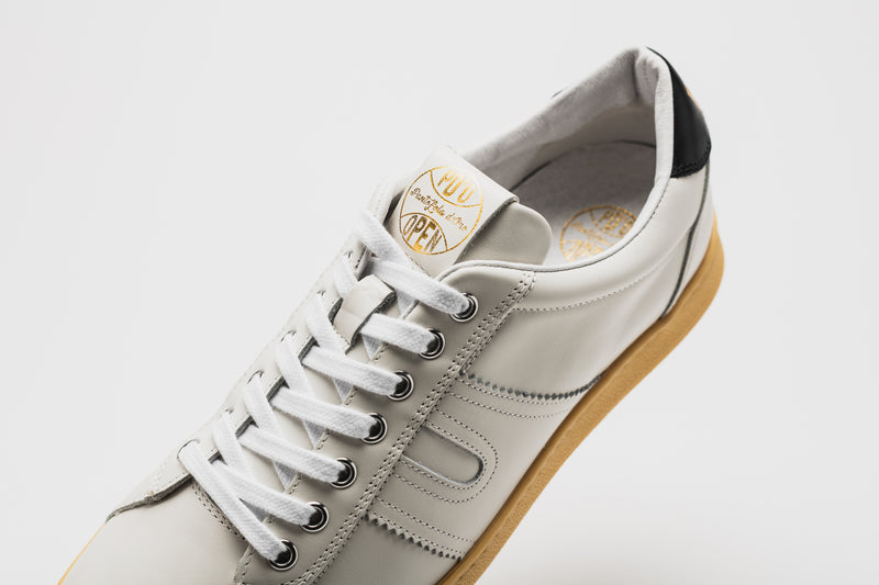 The white lining of a men's leather sneaker set on a pale tan sole