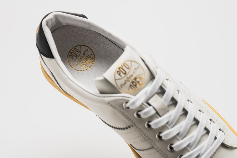 The gold logo detailing on the Open in white leather