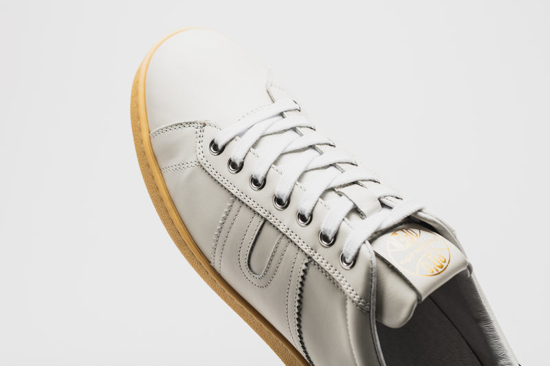 The curved toe section of the Open, with white laces and a pale tan sole