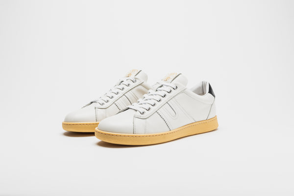 An all-white men's leather sneaker on pale tan soles, with white laces