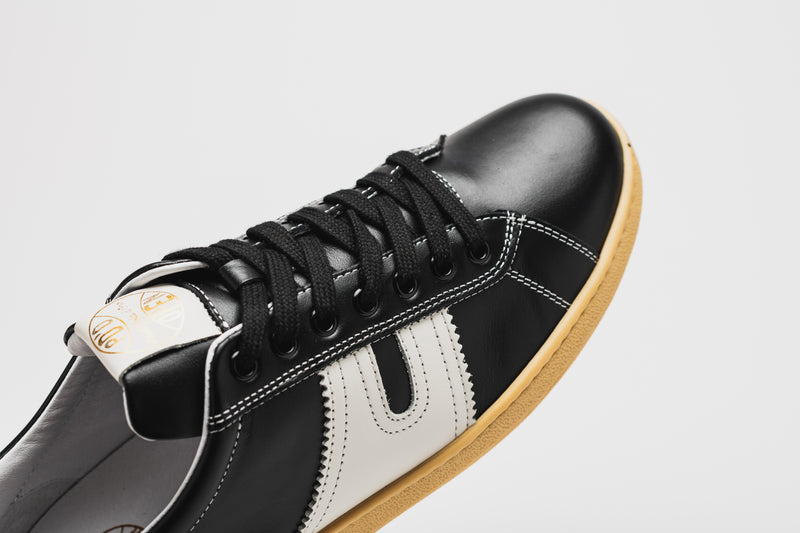 The curved toe of the Open in black leather with white panels on the side