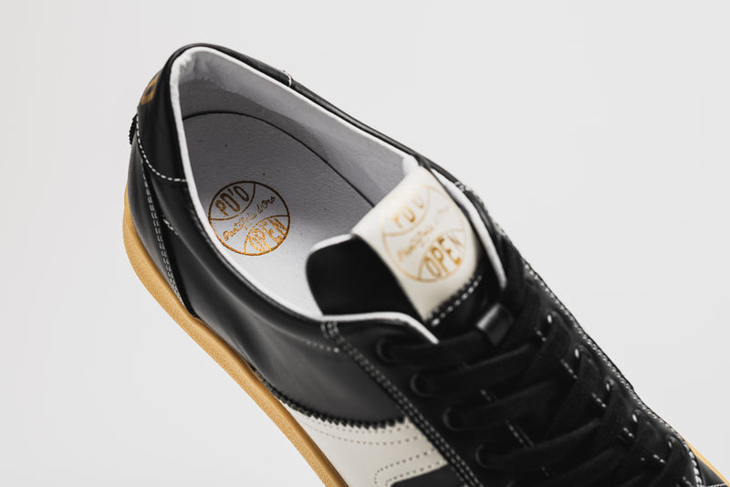 The white lining of the Open with gold logo detailing in the heel section and on the tongue