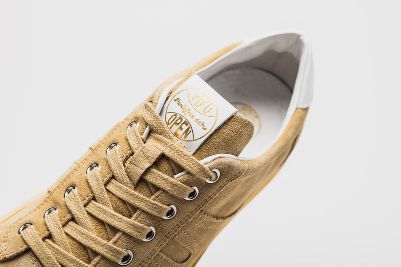 Gold logo detailing on the tongue of a men's suede leather sneaker