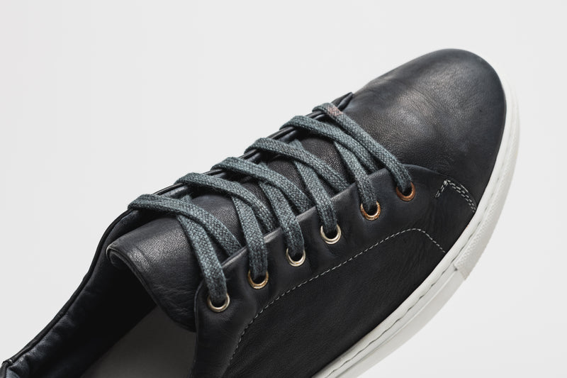 A close-up of the navy blue laces of a men's navy blue leather sneaker