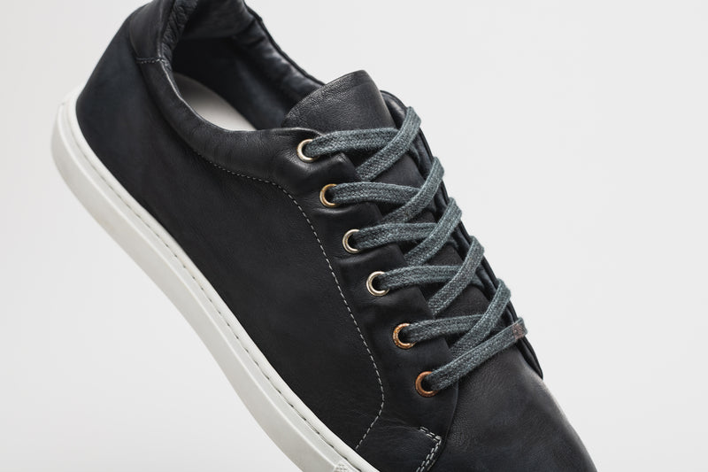 A men's navy blue leather sneaker with a white insole, white sole, and navy blue laces