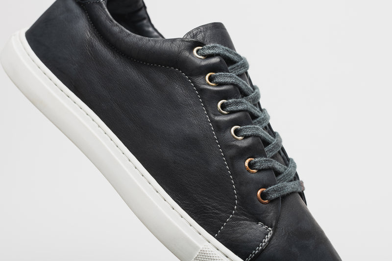 A side image of a men's navy blue leather sneaker, with navy blue laces and a white sole