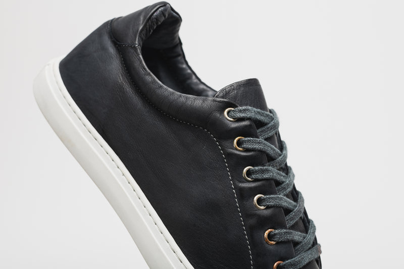 A men's navy blue leather sneaker with navy blue laces and a white sole