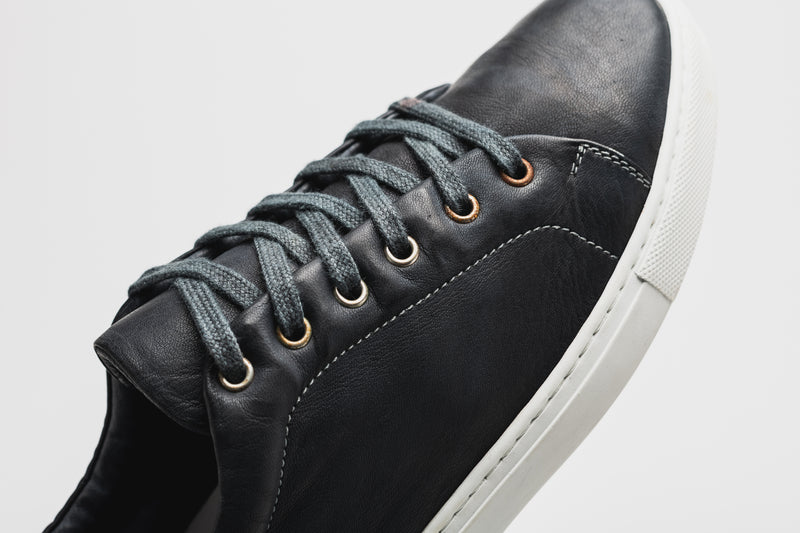 A close-up side image of a men's navy blue leather sneaker with a white sole and navy blue laces
