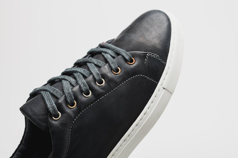 The rounded toe of a men's navy blue leather sneaker