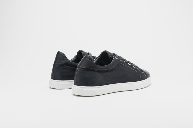 A rear image of navy blue men's leather sneakers on white soles with navy blue laces