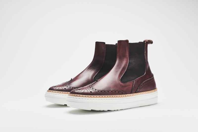 Dark brown, ankle-height Chelsea boots with white sole, brown leather uppers, and black inserts.