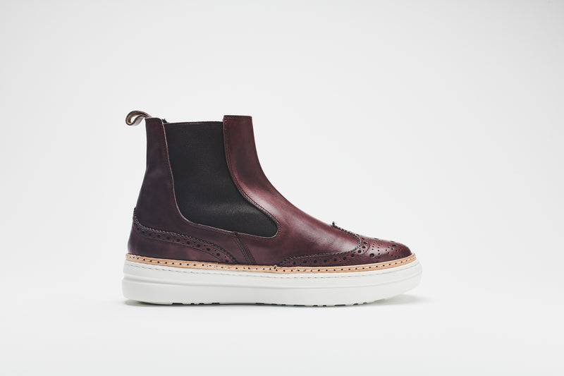 A side image of dark brown, ankle-height Chelsea boots with white sole, brown leather uppers, and black inserts.