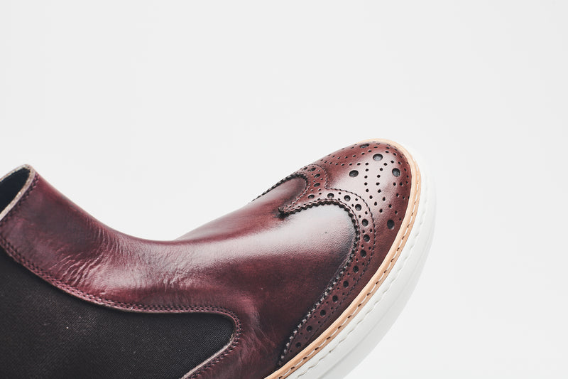 The toe cap of dark brown ankle-height Chelsea boots, decorated with perforations