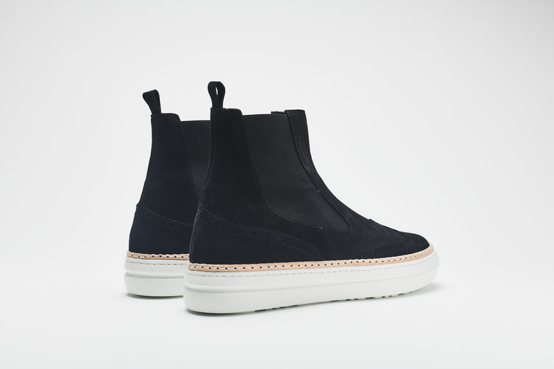 The rear of a navy blue Chelsea boot in supple suede, set on white soles with an elasticated insert