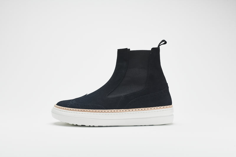 The side of a navy blue Chelsea boot in supple suede, set on white soles with an elasticated insert