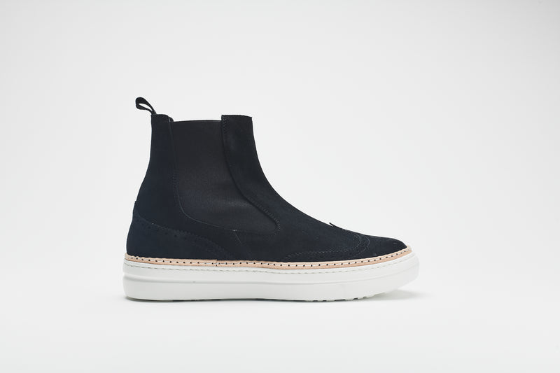 A side image of a navy blue Chelsea boot in supple suede, set on white soles with an elasticated insert