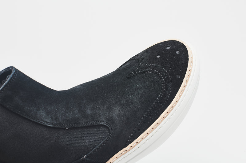 The toe cap of a navy blue Chelsea boot in supple suede, perforated for decoration