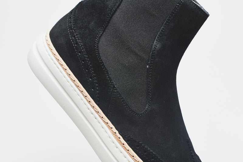 A detailed view of a navy blue Chelsea boot in supple suede, set on white soles with an elasticated insert