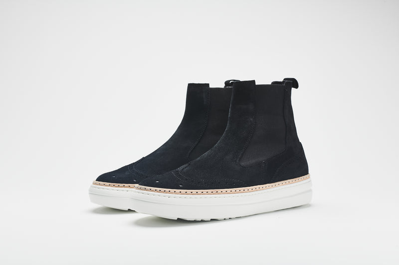 A navy blue Chelsea boot in supple suede, set on white soles with an elasticated insert