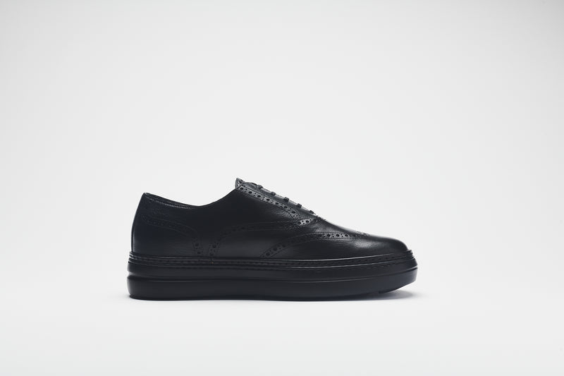 Side image of a chunky leather men's shoe in premium black leather, set on black soles, with black laces