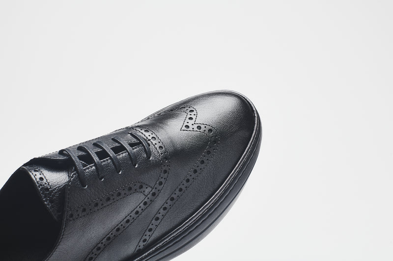A close-up image of the toe-cap of a men's leather shoe, showing perforations that have been added for decoration