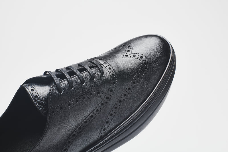 A men's leather shoe, with a toe-cap that features perforations for decoration