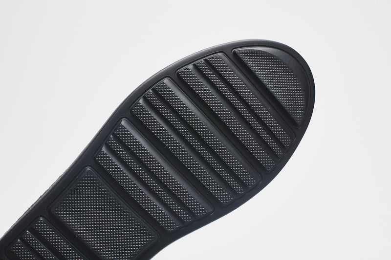 The sole of a men's leather shoe, showing the grooves that enable flexibility for all-day comfort