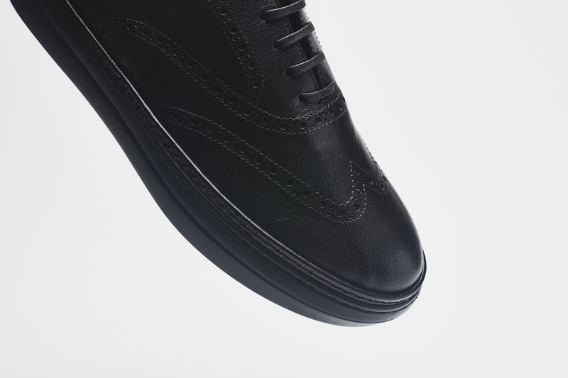 The front of a men's shoes in black leather, on a black sole, with black laces