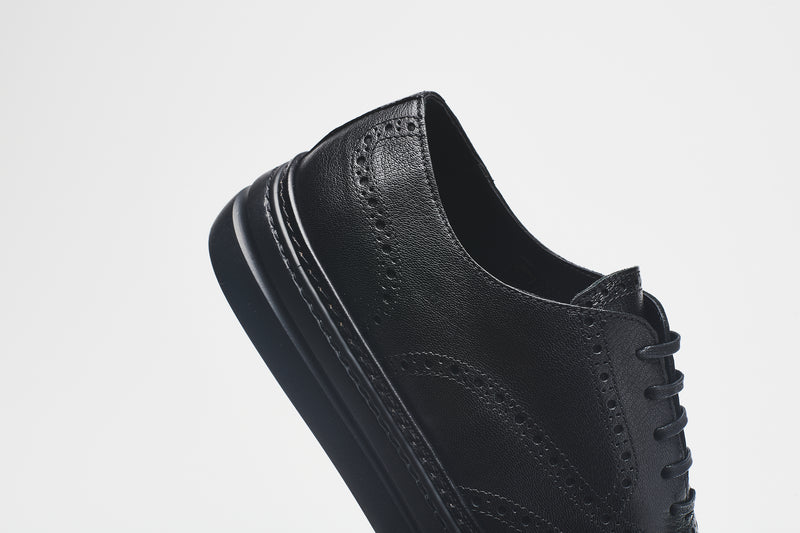 The back section of a chunky leather men's shoe in premium black leather, set on black soles, with black laces